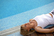 Blond woman laying poolside
