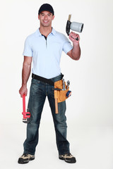 A plumber holding a wielding torch and a wrench.