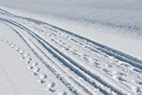 Tire tracks and footsteps in white snow