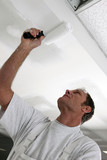 Tradesman painting a ceiling poster