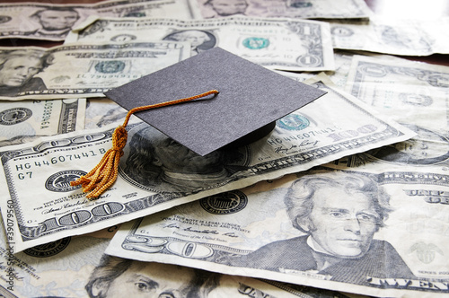 mini college graduation cap on cash