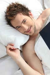 Young man smiling in bed