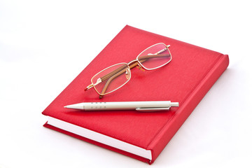 Glasses and the pen on the red book