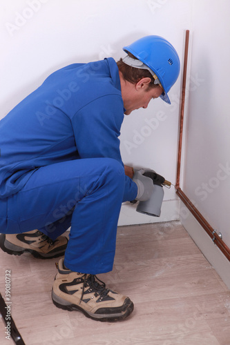 A plumber at work with a blowtorch.