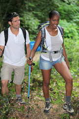 An interracial couple mountain hiking.