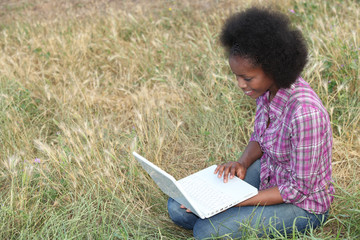 Young woman using a laptop in a field