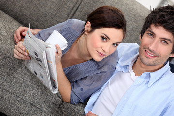 Couple reading a newspaper at home