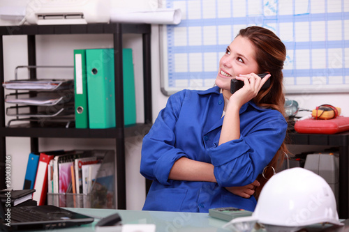 Young woman in blue overalls on the telephone in a depot