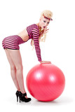 Young woman in modern attire posing with exercise ball