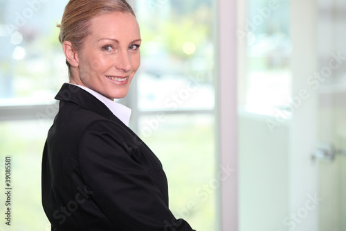 Portrait of a smiling woman in black suit