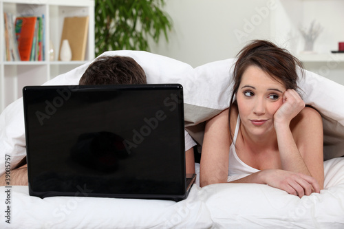 Unimpressed woman in bed with her partner and his laptop