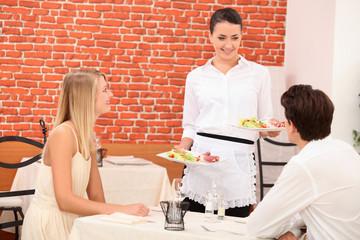 Waitress serving couple