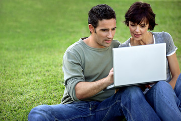 Man and woman on the grass with laptop