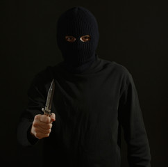 Bandit in black mask with knife isolated on black