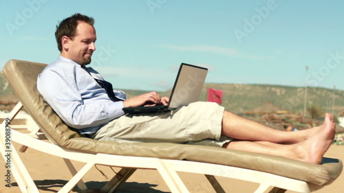 Businessman finishing work on laptop and relaxing on sunbed