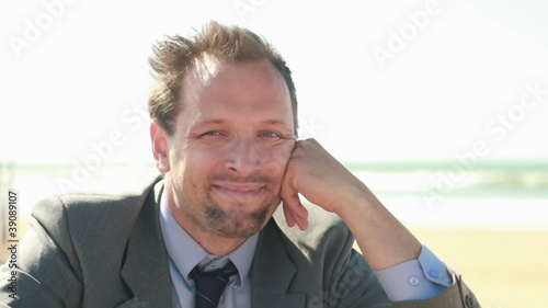 Portrait of happy young businessman sitting on the beach