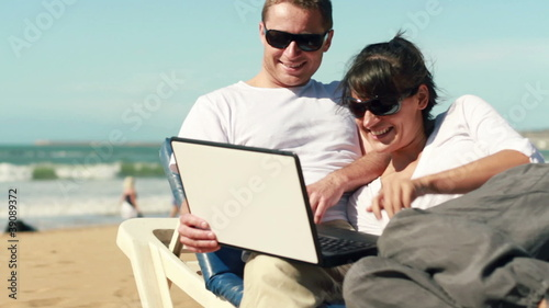 Young happy couple chatting on laptop on the beach