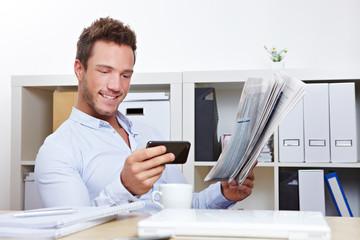 Mann sucht Job mit Zeitung und Smartphone