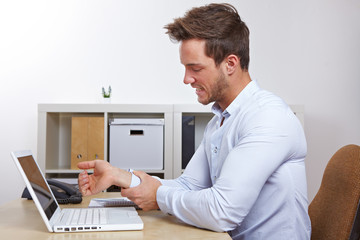 Mann im Büro mit Sehnenscheidenentzündung
