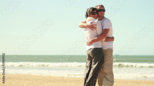 Young happy couple hugging at the beach