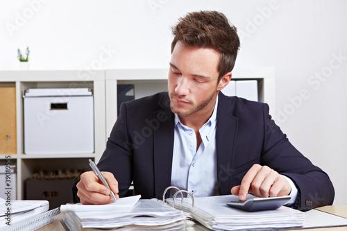 Mann mit Taschenrechner und Akten