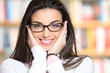 Portrait of beautiful young woman wearing glasses, bookshelf on