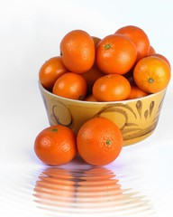 Oranges in an orange ceramic bowl with a reflection