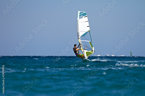 Young male windsurfer in action