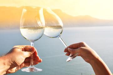 Two hands holding wineglases against Geneva lake, Switzerland