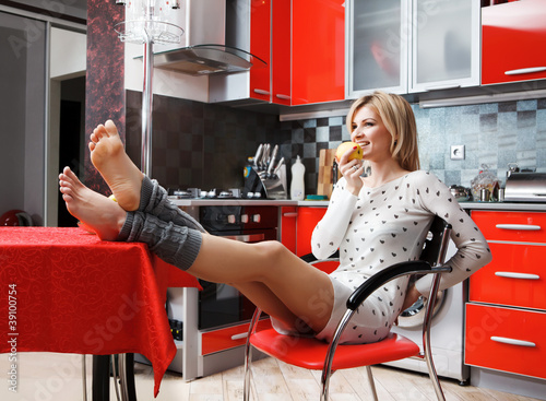 Pretty smiling young woman sit in the kitchen with fruit
