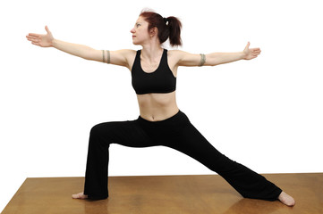 Woman in yoga warrior posture on a blue rug