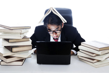 Stressed businessman in working with books