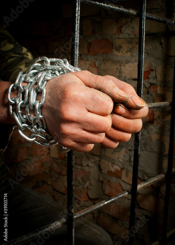 Man with hands tied up with chains