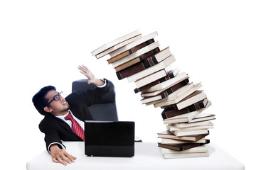 Scared businessman with pile of books
