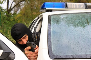 Policeman shoots from the police vehicle, detail
