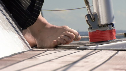 Leg on the deck of the  sailboat