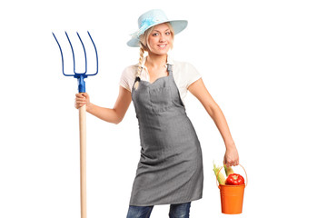 A female farmer holding a pitchfork and bucket with vegetables
