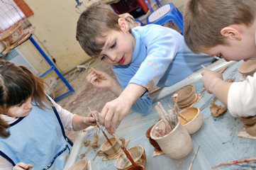 group of hildren shaping clay in pottery studio