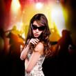 junge brünette Frau mit Sonnenbrille vor Party-Hintergrund