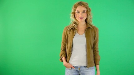 Young woman on green background talking to camera