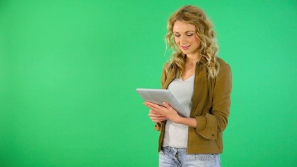 Beautiful young woman using tablet on green background