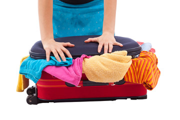 Woman crammed full of clothes in red suitcase