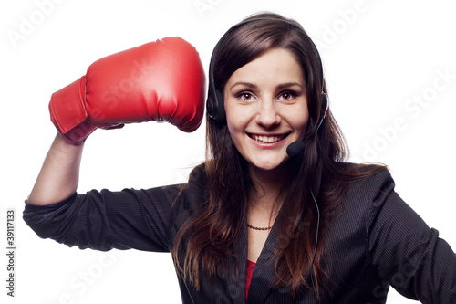 Businesswoman hitting herself with boxing gloves
