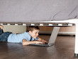 Child playing laptop under the bed