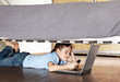 Child with laptop and phone under the bed