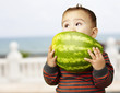 portrait of a handsome kid holding watermelon and sucking near t