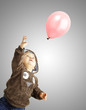 portrait of funny kid trying to hold a pink balloon over grey ba