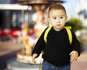 portrait of adorable kid carrying yellow backpack against a caro