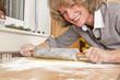 lachende Hausfrau rollt Teig aus