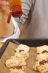 Hausfrau bringt Schokoguss auf Kekse auf